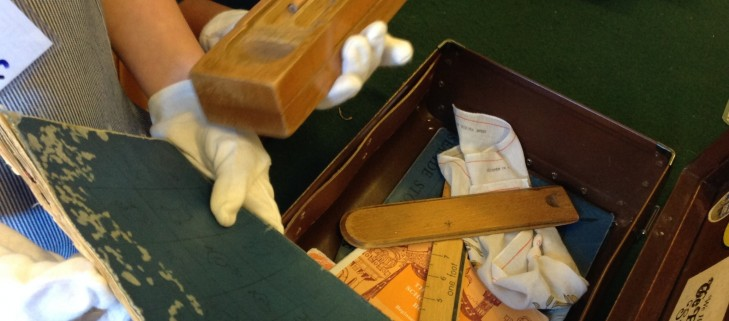 Students wearing cotton gloves to examine old objects in school cases