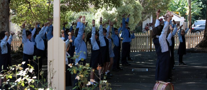 A class learns drill outside using wooden dumb bells