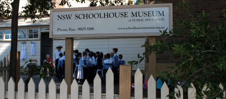 A visiting class lines up outside the Schoolhouse Museum