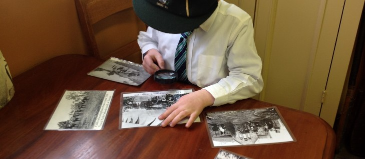 Students use magnifiers to examine early photographs of school children