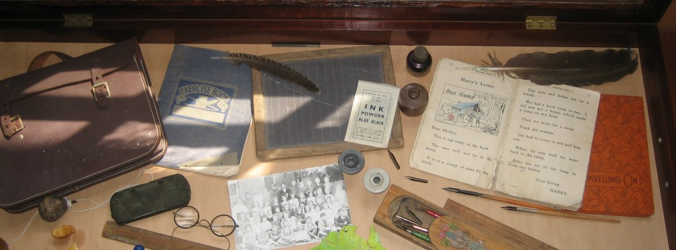 A display case showing early writing technologies such as pen and ink, timber pencil box, wooden ruler, blotting paper, glasses and ink powder sachet
