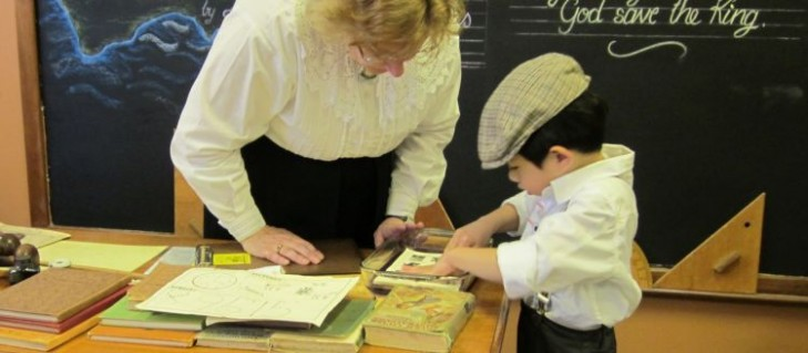 A young boy in heritage costume placed his worksheet on the jelly pad to obtain a print of a map