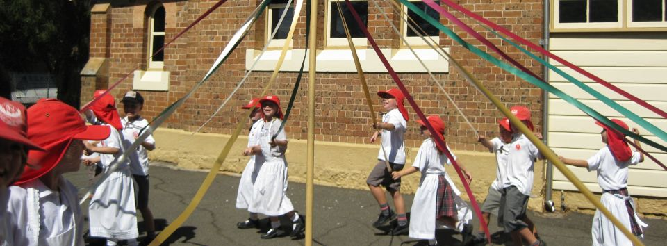 Students wear pinafores and sailor collars when dancing around the maypole outside the museum