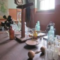 A collection of old bottles, a set of scales, a stereoscope and a bar bell on a wooden desk