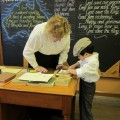 Museum teacher helping student use the jelly pad.