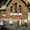 Students skipping around the maypole in front of the NSW Schoolhouse Museum