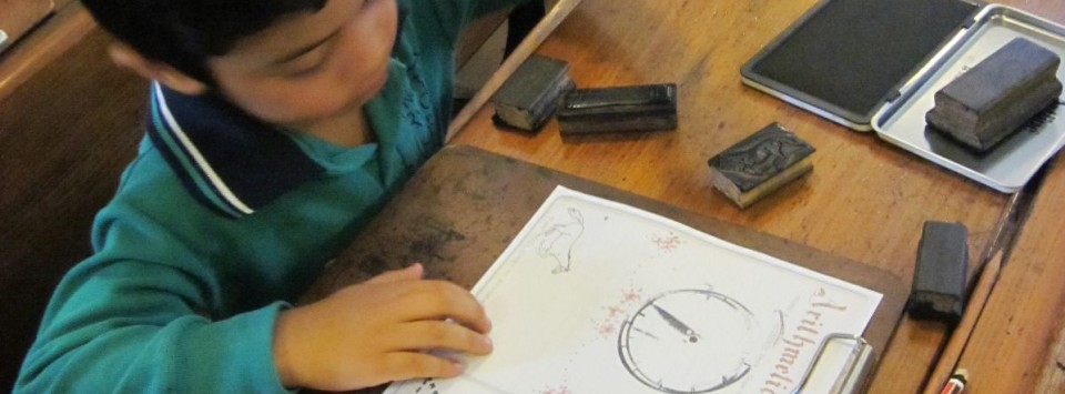 Student using stamps and a stamp pad to complete an Arithmetic task.
