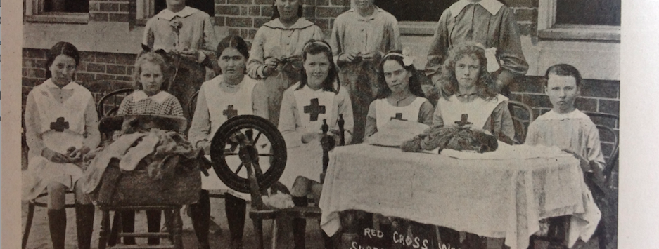 Red Cross workers of Coonamble Superior School with spinning wheel and knitted socks for the war effort. From Education Gazette January 1918