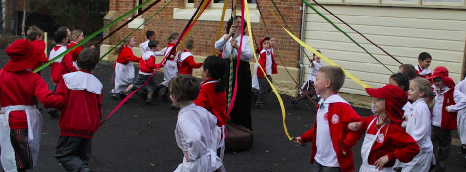Young girls and boys skipping around a maypole.