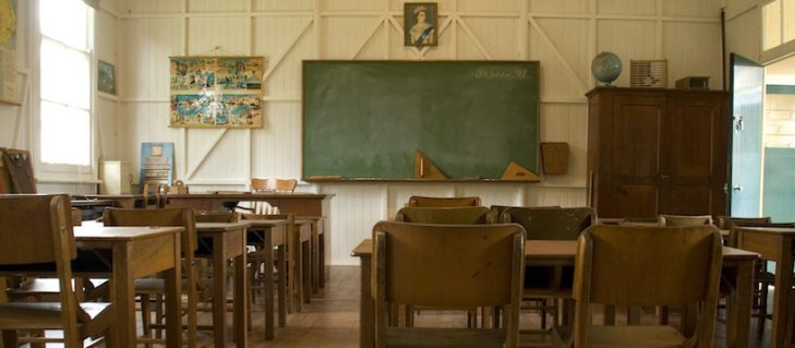 Classroom with timber chairs and desks, blackboard on front wall and photo of a young Queen Elizabeth