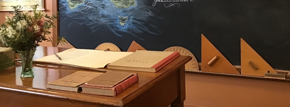 Wooden teachers desk with chalkboard in background. Teachers's books and a vase of flowers on the desk. Wooden chalk stencils lean against the chalkboard.