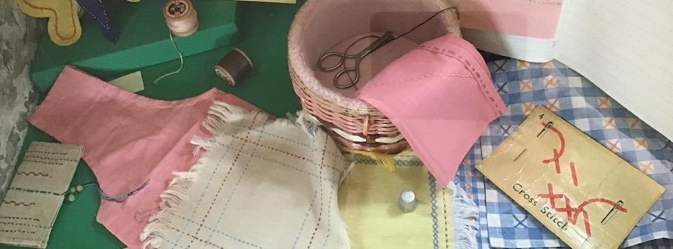 Needlework materials. A basket , thread, cross stitch examples