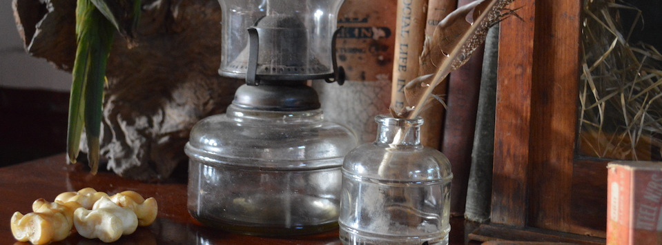 A collection of Knucklebones or jacks , Kerosene lamp and glass inkwell on a wooden desk.