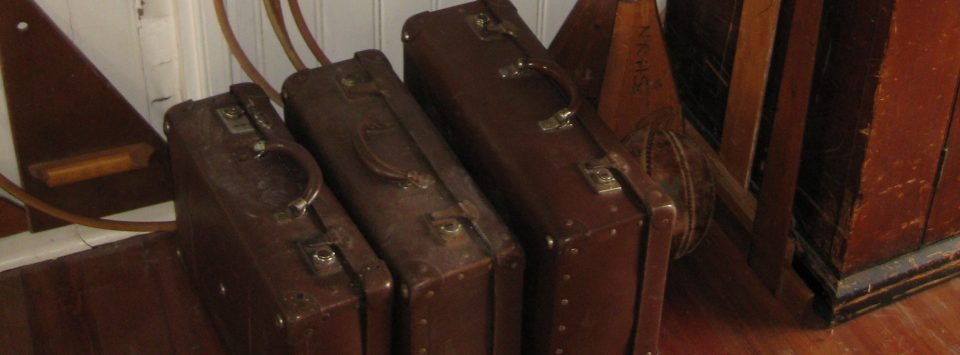 Three Globite suitcases placed at the front of a classroom.