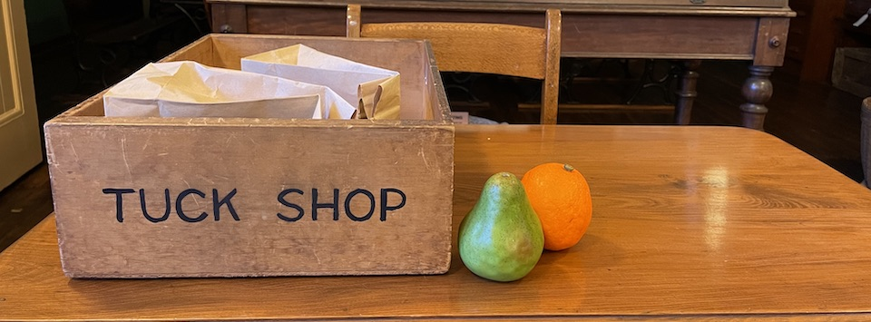 Wooden box with Tuck Shop written on front . Box contains brown paper bags .A pear and orange is on a wooden desk
